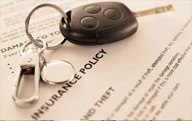 Car keys on top of insurance papers
